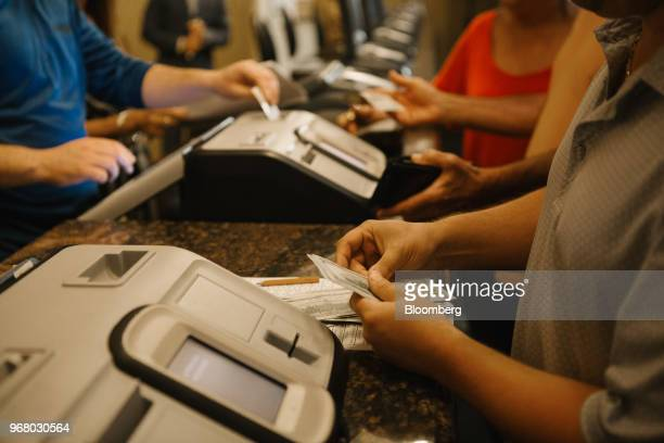 A guest holds US one hundred dollar banknotes before placing a bet during the launch of fullscale sports betting at Dover Downs Hotel and Casino in...