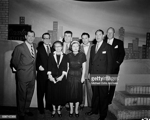 """Guest host Milton Berle with cast pose with Mrs Knute Rockne and her daughter during rehearsals for """"The Toast of the Town"""" hosted by Ed Sullivan in..."""