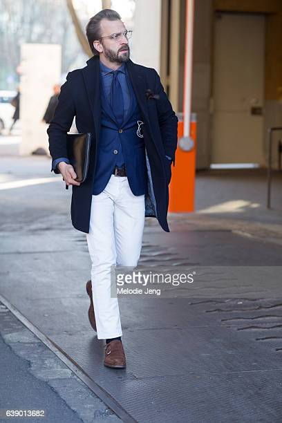 A guest in a blue coat blue blazer shirt and tie white pants and brown monk strap shoes during Milan Men's Fashion Week Fall/Winter 2017/18 on...