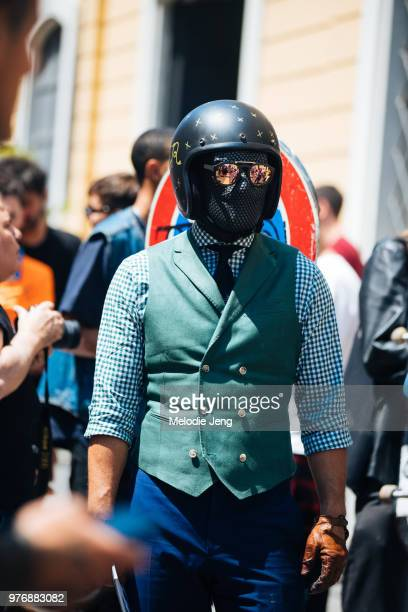 A guest in a motorcycle helmet and his face covered during Milan Men's Fashion Week Spring/Summer 2019 on June 16 2018 in Milan Italy
