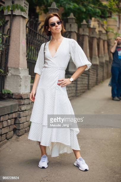 A guest in a white striped dress and white chunky net sneakers on May 5 2018 in Tbilisi Georgia