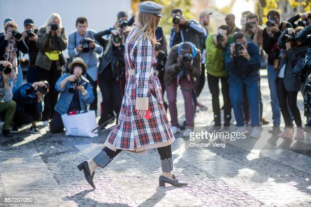 A guest in front of photographers wearing plaid trench coat flat cap seen outside Chanel during Paris Fashion Week Spring/Summer 2018 on October 3...