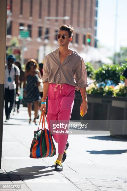 Guest in pink pants and a Balenciaga bag during New York Fashion Week Mens Spring/Summer 2019 on July 9, 2018 in New York City.