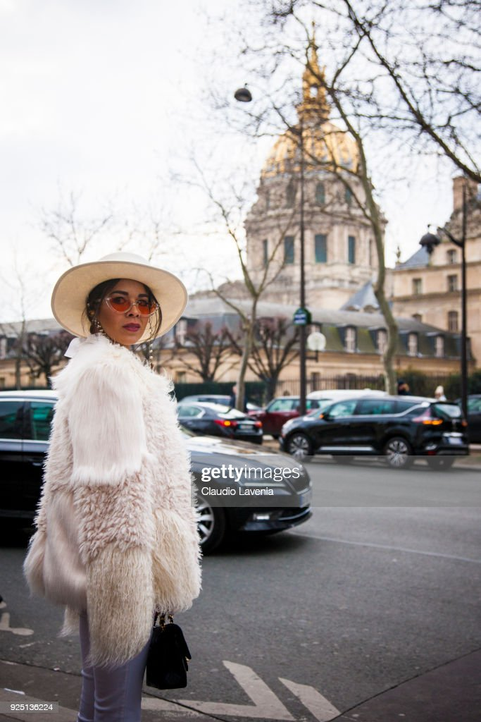 A guest in total white wears white fur coat and Chanel black bag is seen on the streets of Paris after the Dior show during Paris Fashion Week Womenswear Fall/Winter 2018/2019 on February 27, 2018 in Paris, France.