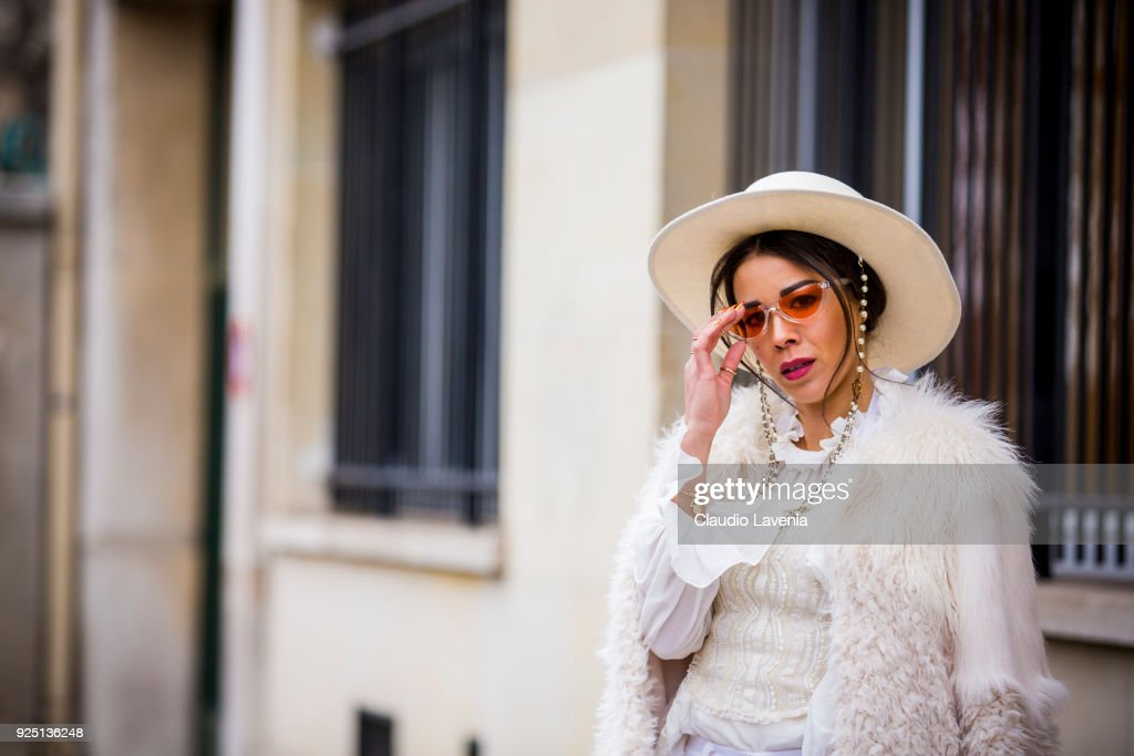 A guest in total white wears white fur coat on the streets of Paris after the Dior show during Paris Fashion Week Womenswear Fall/Winter 2018/2019 on February 27, 2018 in Paris, France.