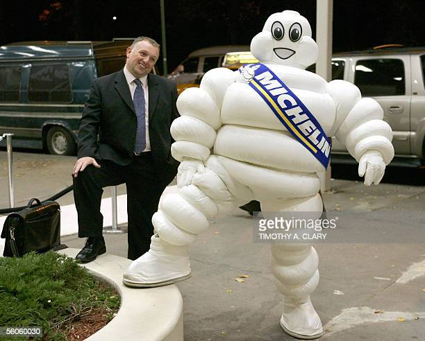 A guest is mimiked by the Michelin Man outside the Guggenheim Museum in New York city 02 November 2005 during a party to launch the first Michelin...