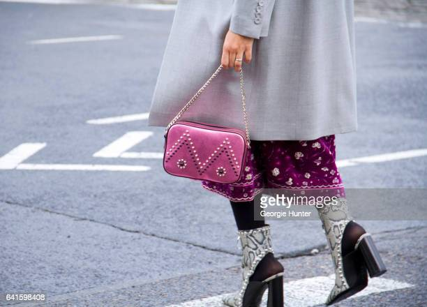 Guest is seen at Spring Studios outside the Lacoste show wearing high waisted purple floral three quarter length skirt pastel blue coat pink bag with...