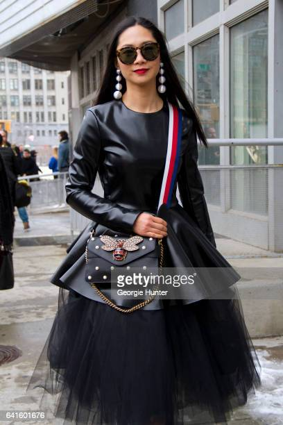 Guest is seen at Spring Studios outside the Lacoste show wearing black patent dress with large under skirt black studded bag with jeweled bee and...