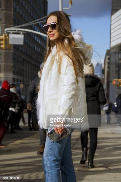 Guest is seen at Spring Studios outside the Phillip Lim show wearing white faux fur coat with clear plastic rain jacket with hood denim jeans black...