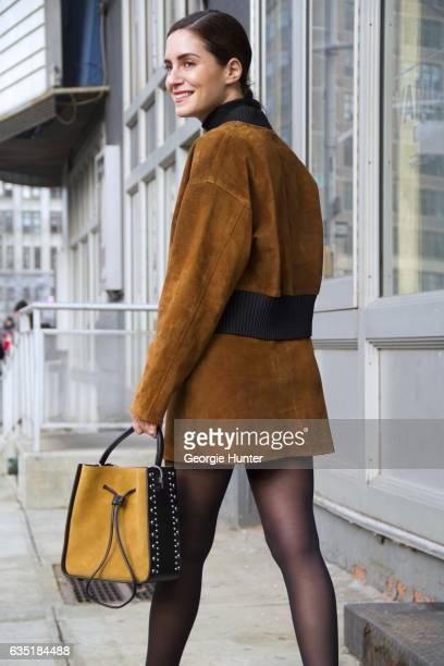 Guest is seen at Spring Studios outside the Phillip Lim show wearing tan suede skirt and bomber jacket with black large ribbed collar and hem and...