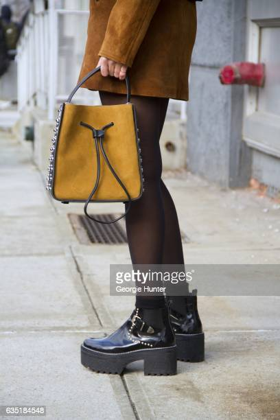 Guest is seen at Spring Studios outside the Phillip Lim show wearing tan suede skirt and bomber jacket with black large ribbed collar and hem black...