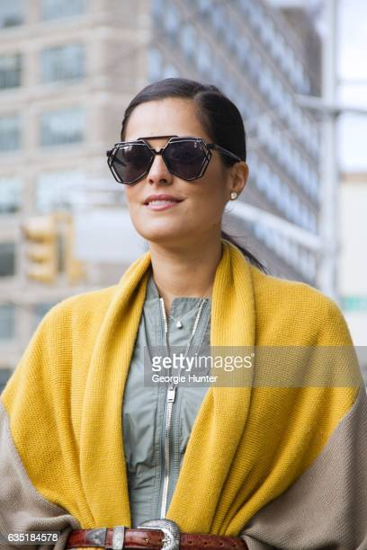 Guest is seen at Spring Studios outside the Phillip Lim show wearing geometric black sunglasses green dress with front zip and brown and yellow knit...