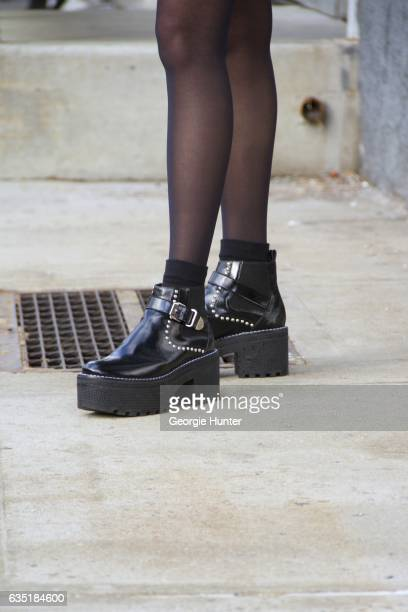 Guest is seen at Spring Studios outside the Phillip Lim show wearing black patent platform ankle booties with chunky heel silver buckles and silver...