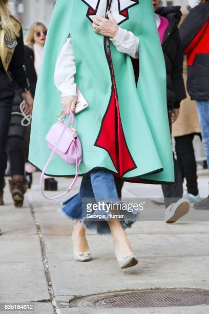 Guest is seen at Spring Studios outside the Phillip Lim show wearing mint green white and red cape with black seams pink bag with thin strap carry...