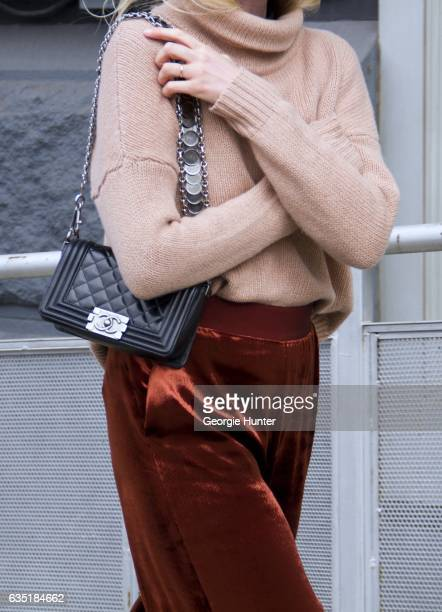 Guest is seen at Spring Studios outside the Phillip Lim show wearing rust color high waist velvet pants black leather Chanel bag with silver buckle...