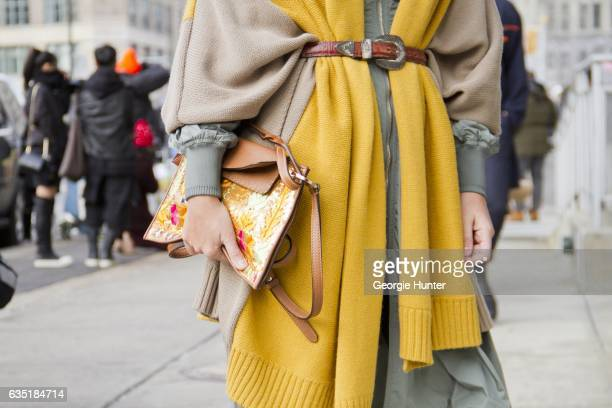Guest is seen at Spring Studios outside the Phillip Lim show wearing green dress with front zip brown and yellow knit shawl with brown cowboy waist...