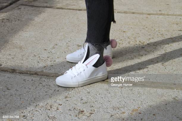Guest is seen at Spring Studios outside the Phillip Lim show wearing black denim jeans with frayed hem and white leather laceup sneakers with bunny...