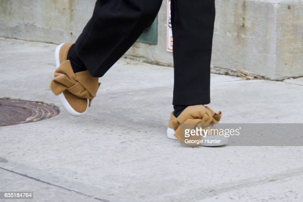 Guest is seen at Spring Studios outside the Phillip Lim show wearing brown fabric sneakers with oversized tie on February 13 2017 in New York City
