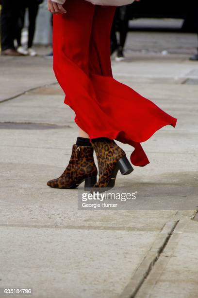 Guest is seen at Spring Studios outside the Phillip Lim show wearing red flared pants with slit and leopard print ankle booties with black block heel...