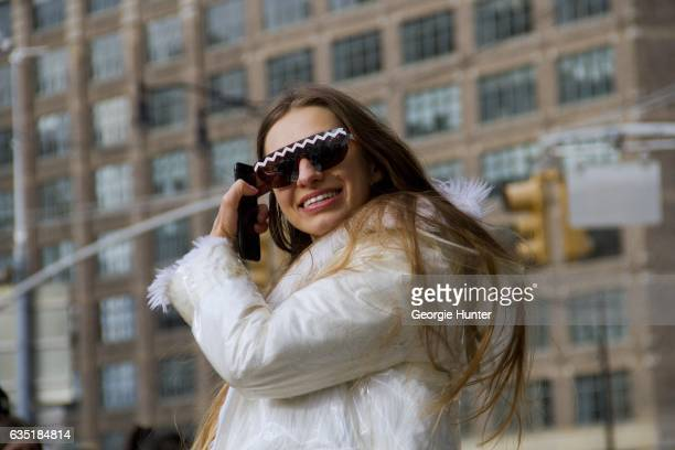 Guest is seen at Spring Studios outside the Phillip Lim show wearing white faux fur coat with clear plastic rain jacket with hood and black statement...