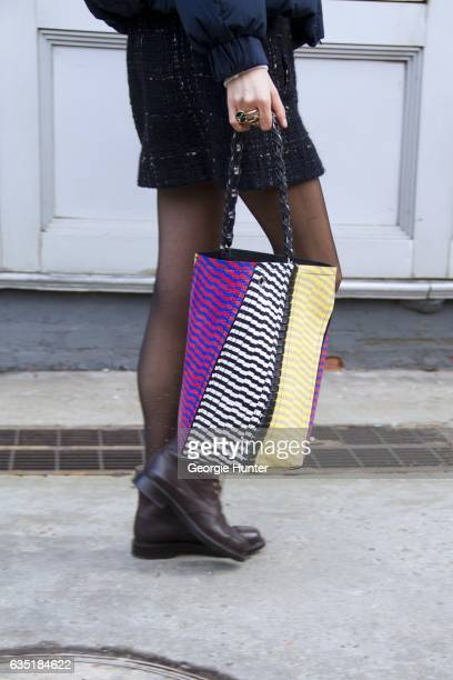 Guest is seen at Spring Studios outside the Phillip Lim show with multi colored patch patterned bag on February 13 2017 in New York City