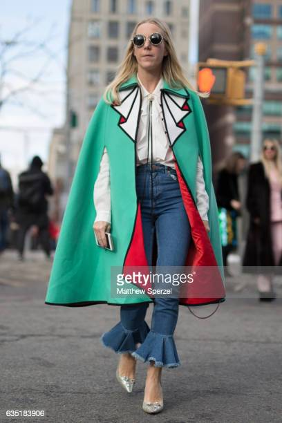 A guest is seen attending 31 Phillip Lim during New York Fashion Week wearing a green red and white cape coat with bell bottom jeans on February 13...