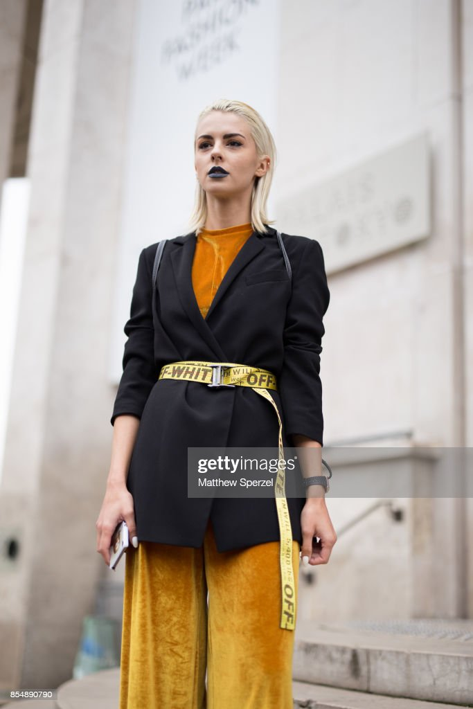 A guest is seen attending AALTO during Paris Fashion Week wearing a black blazer, gold pants and Off-White belt on September 27, 2017 in Paris, France.
