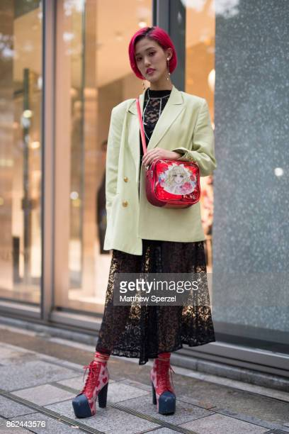 A guest is seen attending AKIKOAOKI during Tokyo Fashion Week wearing a neon jacket with shear black dress and vintage kawaii bag on October 17 2017...