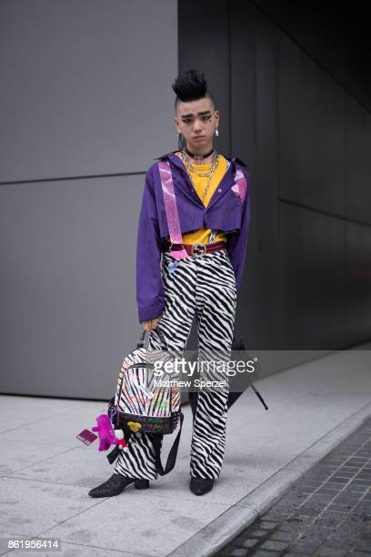 A guest is seen attending Asia Fashion Collection during Tokyo Fashion Week wearing a purple jacket with zebra stripe pants and yellow shirt on...