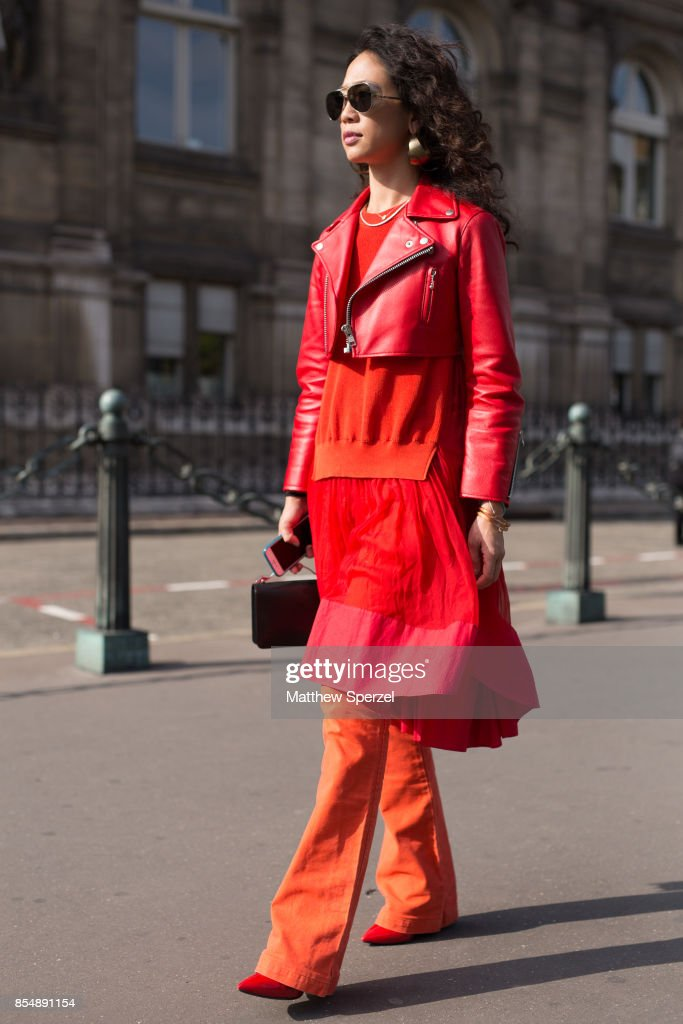 A guest is seen attending Dries Van Noten during Paris Fashion Week wearing a red and orange outfit on September 27, 2017 in Paris, France.