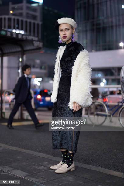 A guest is seen attending Fashion Hong Kong during Tokyo Fashion Week wearing a black dress with white fur coat and black and white hat on October 17...
