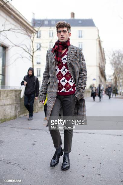 A guest is seen attending Issey Miyake during Men's Paris Fashion Week AW19 wearing argyle sweater red scarf grey coat and slacks with black shoes on...
