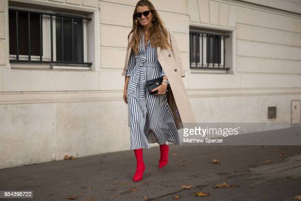 A guest is seen attending JOUR/N during Paris Fashion Week wearing a black and white striped dress with red boots on September 26 2017 in Paris France