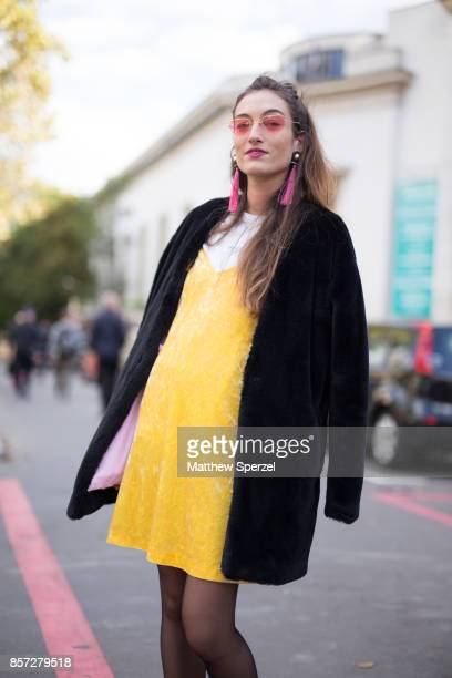 A guest is seen attending Junko Shimada during Paris Fashion Week wearing a yellow velvet jumper with black coat on October 3 2017 in Paris France