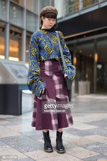 A guest is seen attending KEISUKEYOSHIDA during Tokyo Fashion Week wearing a blue and yellow pattern top with maroon plaid skirt on October 17 2017...