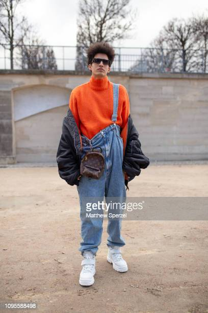 A guest is seen attending Louis Vuitton during Men's Paris Fashion Week AW19 wearing orange turtleneck with denim overalls and black coat with Louis...