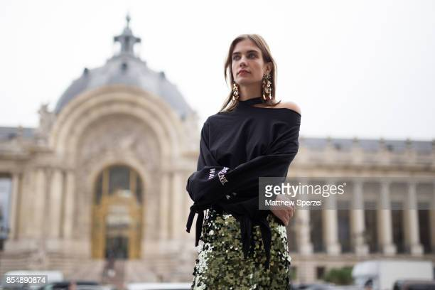 A guest is seen attending Maison Margiela during Paris Fashion Week wearing a black shirt with green sequin skirt on September 27 2017 in Paris France