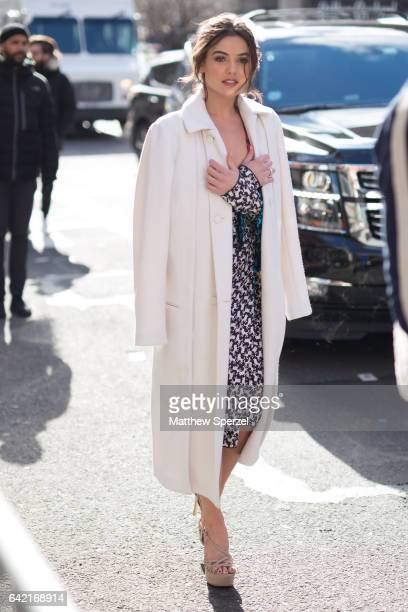 Guest is seen attending Marc Jacobs during New York Fashion Week wearing a long white coat with black and gold dress on February 16, 2017 in New York...
