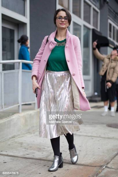 A guest is seen attending Michael Kors during New York Fashion Week wearing a pink coat with green top and silver skirt and shoes on February 15 2017...