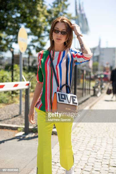 A guest is seen attending Rebekka Ruetz wearing a colorful striped shirt with yellow pants during the Berlin Fashion Week July 2018 on July 4 2018 in...