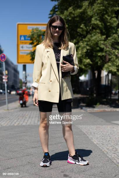 A guest is seen attending Rebekka Ruetz wearing a light yellow blazer with black shirt and spandex shorts during the Berlin Fashion Week July 2018 on...