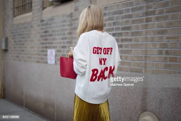 A guest is seen attending Son Jung Wan during New York Fashion Week wearing a white and red 'Get Off My Back' sweater with red bag and long gold...