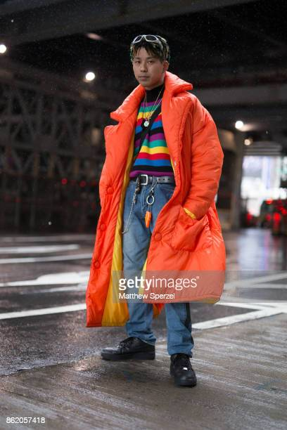 A guest is seen attending YOHEI OHNO and DRESSEDUNDRESSED during Tokyo Fashion Week wearing an orange down coat with blue jeans and stripe multicolor...