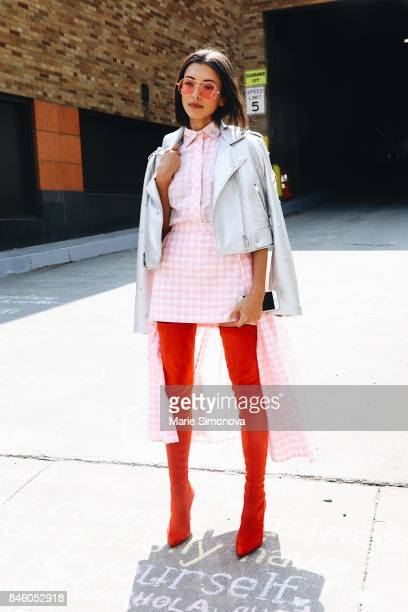 Guest is seen before runway show wearing long red boots white jacket and dress during New York Fashion Week on September 11 2017 in New York City