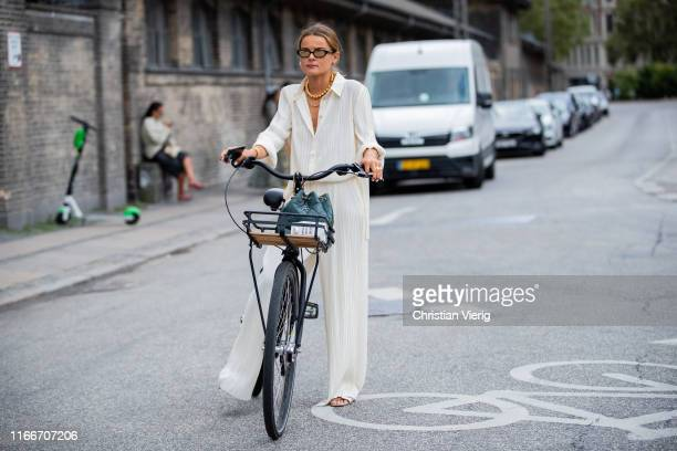 Guest is seen on her bike outside Holzweiler during Copenhagen Fashion Week Spring/Summer 2020 on August 07, 2019 in Copenhagen, Denmark.
