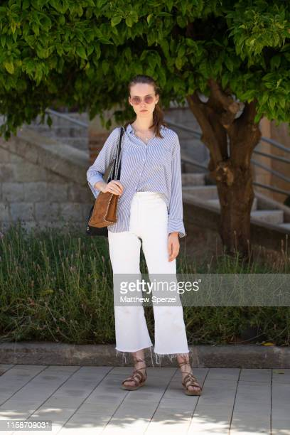 A guest is seen on the street attending 080 Barcelona Fashion Week wearing a blue striped shirt white frayed jeans brown bag and sandals on June 27...