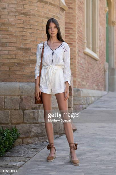 A guest is seen on the street attending 080 Barcelona Fashion week wearing white dress with brown heels on June 25 2019 in Barcelona Spain