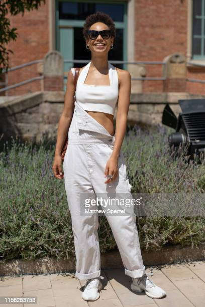 A guest is seen on the street attending 080 Barcelona Fashion week wearing white crop top white overalls and white sneakers on June 25 2019 in...