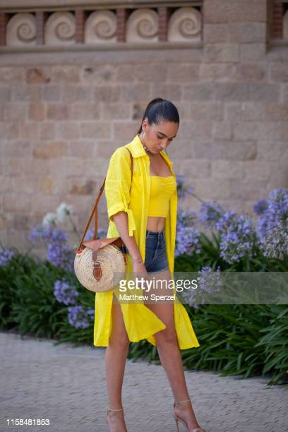 Guest is seen on the street attending 080 Barcelona Fashion Week wearing yellow long shirt, yellow crop top and denim shorts with straw circular bag...
