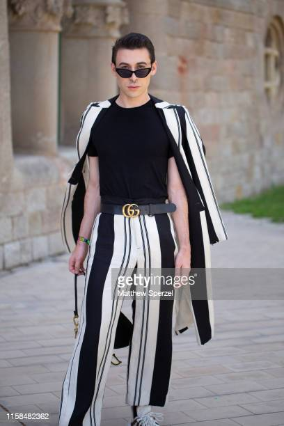 A guest is seen on the street attending 080 Barcelona Fashion Week wearing black/white stripe coat and pants with black tshirt and black Dior bag on...